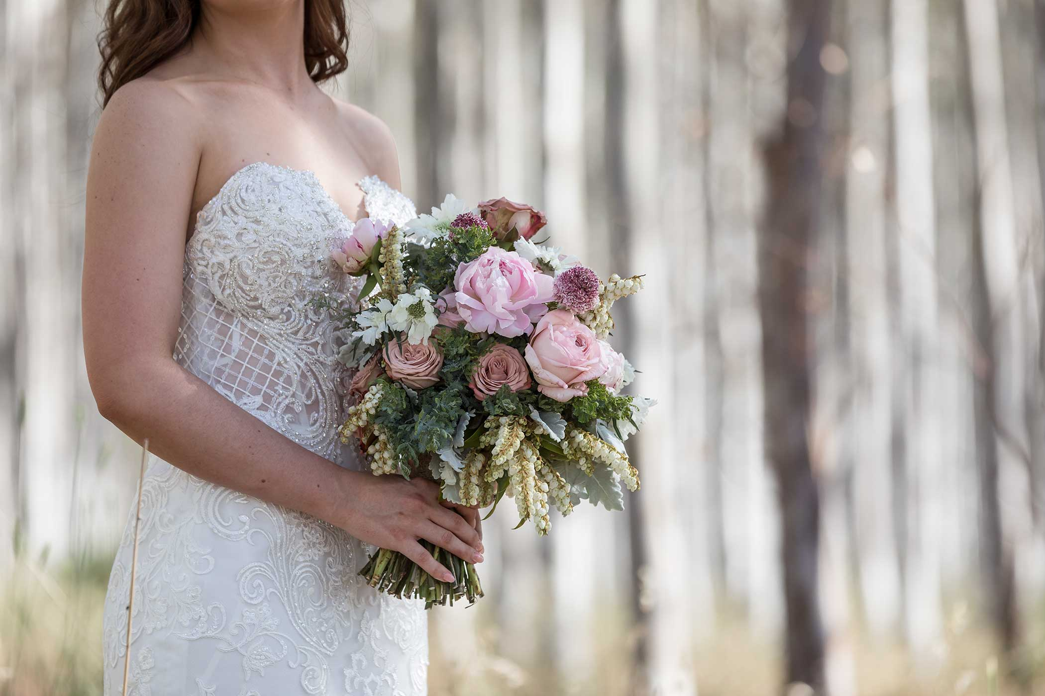 Close up of Bride with beaded gown holding flowers