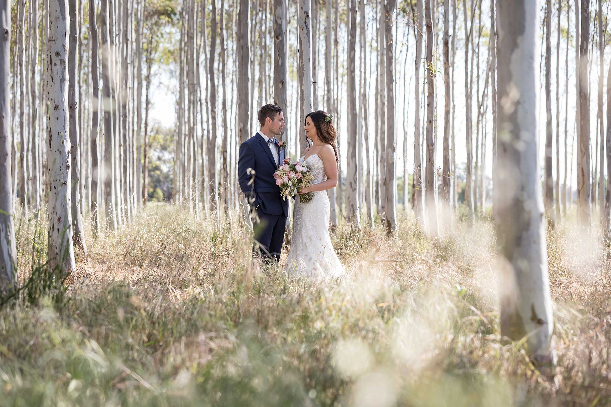 Bride and Groom standing in tall trees in sunlit forest
