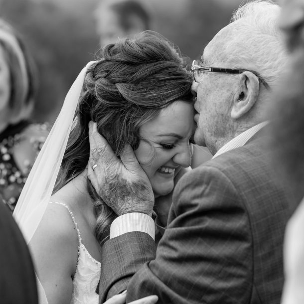 Grandfather kissing Brides forehead after wedding ceremony