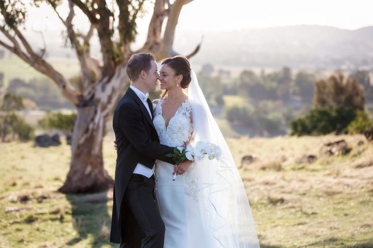 Bride with long veil and orchids and Groom with coat and tails on hill in sunlight