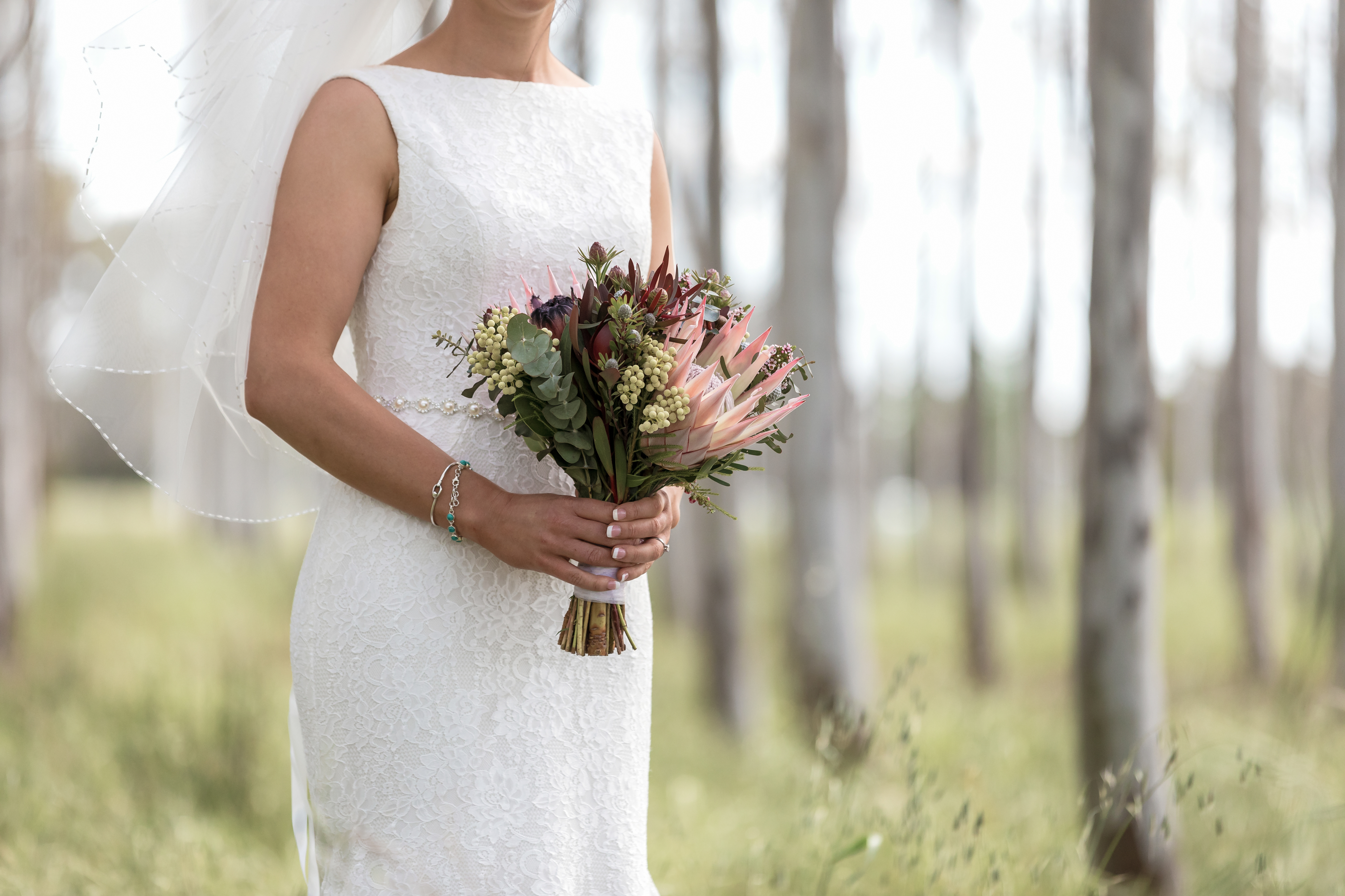Bride in lace gown holding native flowers