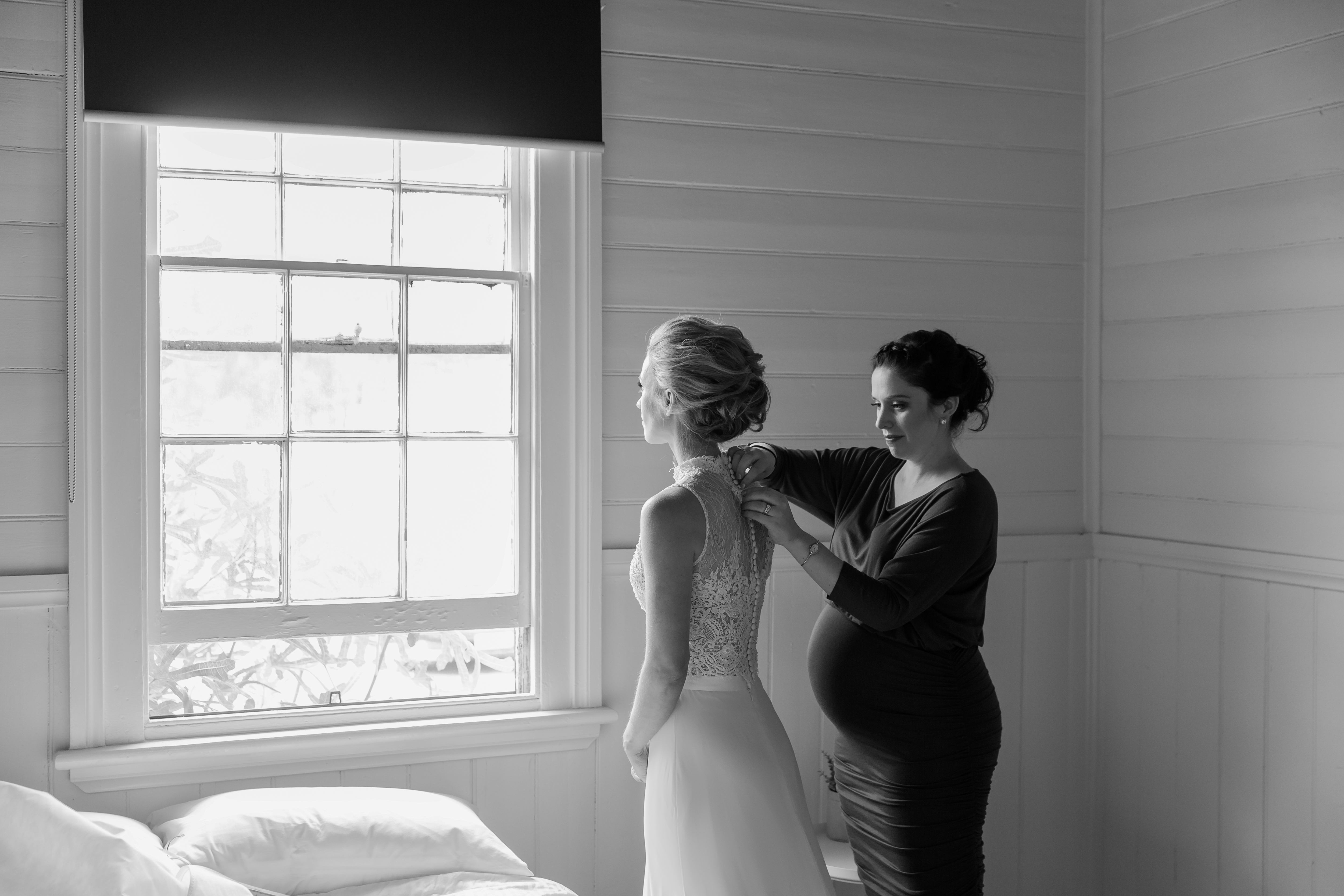 Bridesmaid helping Bride with Wedding gown