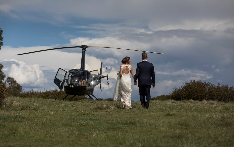 Bride and Groom holding hands walking to helicopter in Alpine area