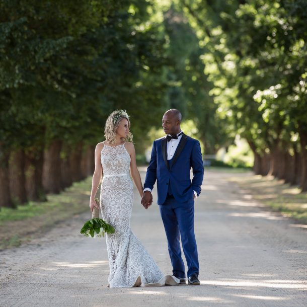 Bride and Groom walking down long driveway of All Saints Estate