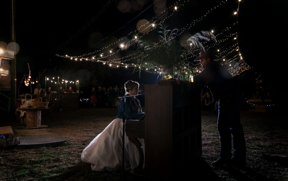 Bride playing open air piano under fairylights with groom