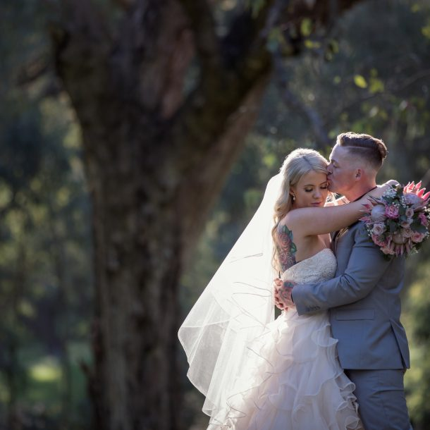 Bride with ruffled gown and Groom with natural setting backdrop