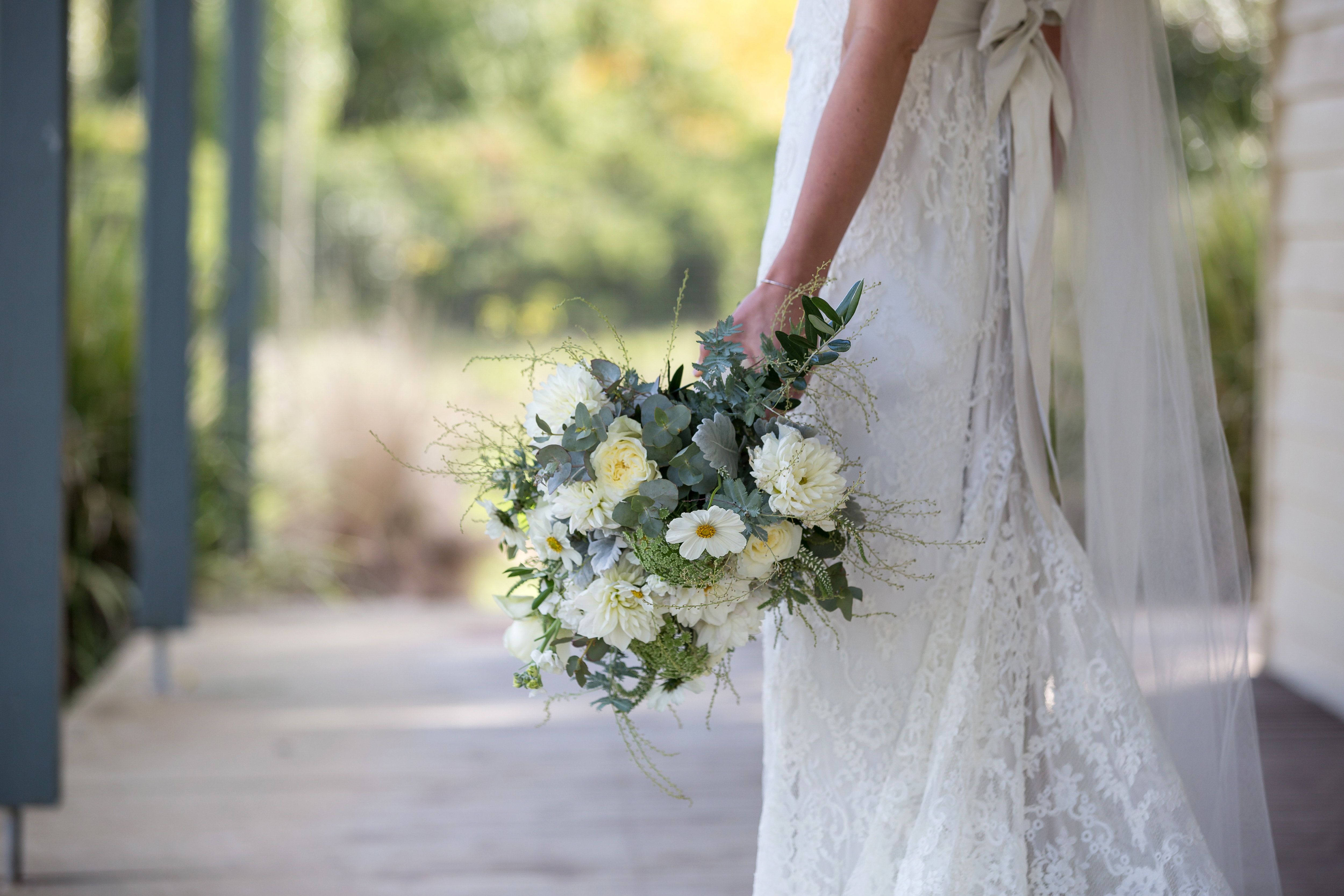 Bride wearing lace gown and ribbon sash holding wedding flowers
