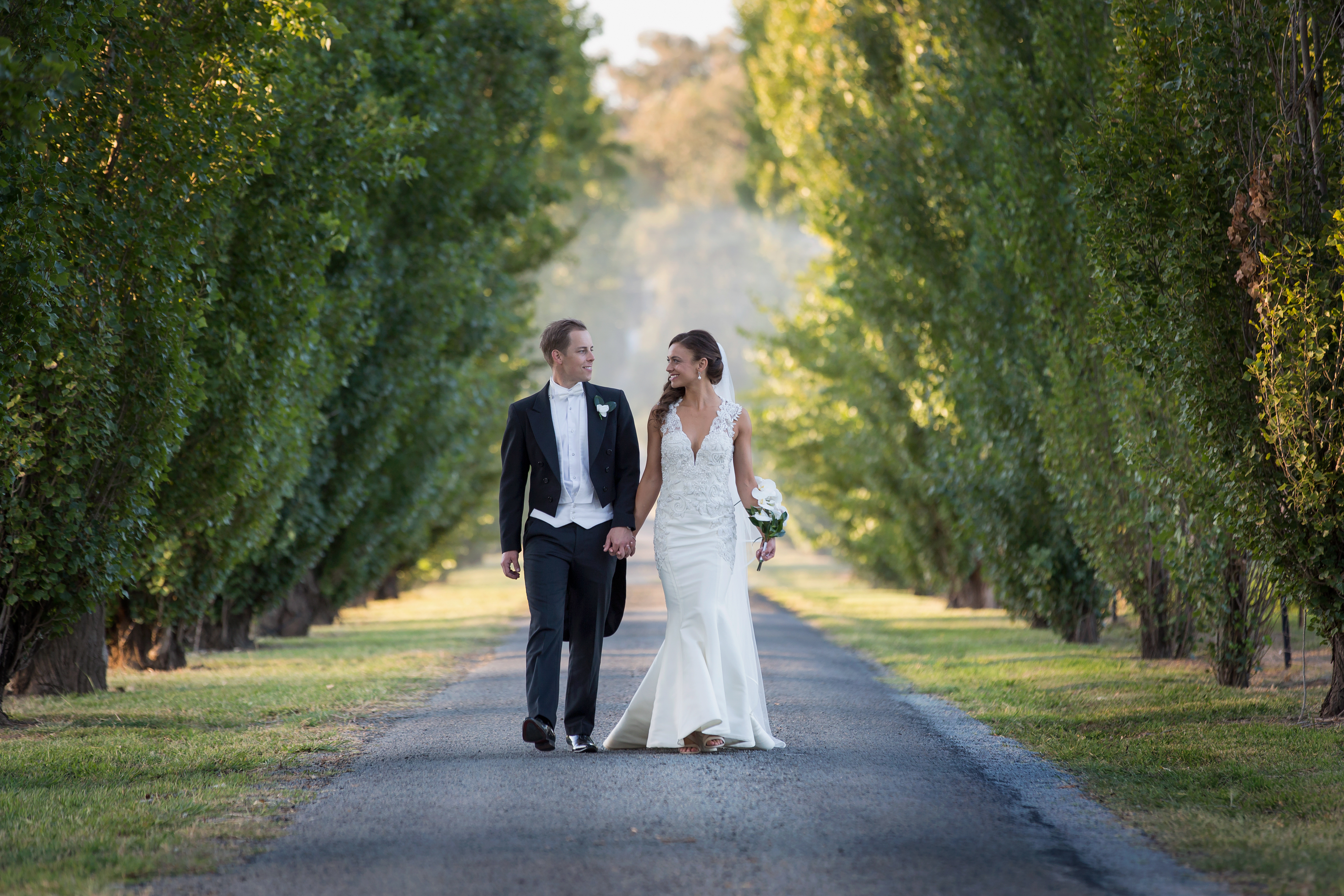 Bride and Groom in coat and tails walking down formal driveway