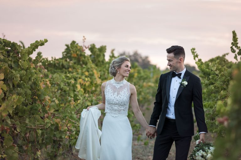 Bride and Groom walking through vines