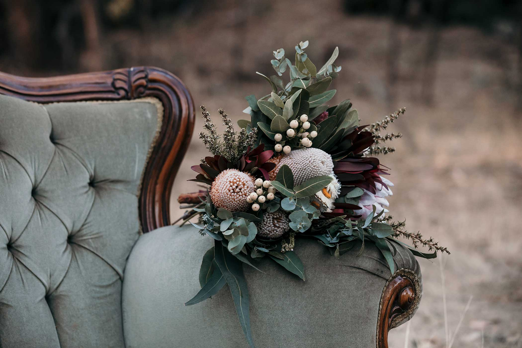 Native wedding flower bouquet resting on vintage chair