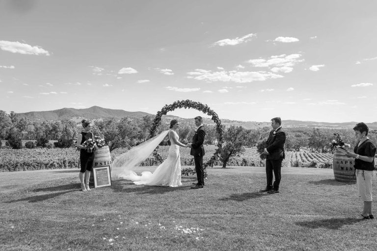 Bride and Groom at wedding ceremony with large floral wreath backdrop in vineyard