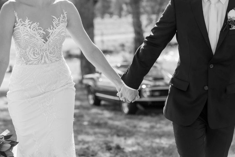 Bride and Groom holding hands with classic car in background