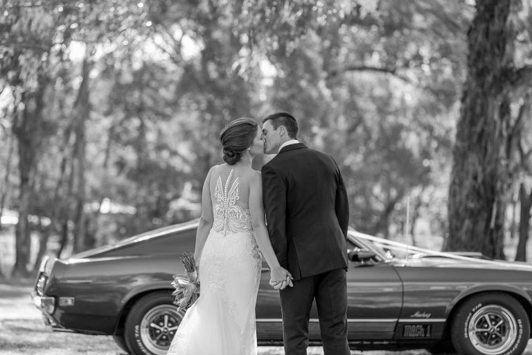 Bride and Groom kissing with classic car in background