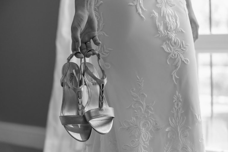 Bride holding silver strap wedding shoes