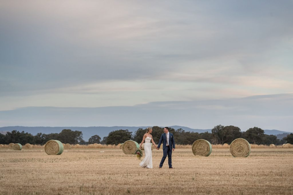Bride and groom in field with hay bales